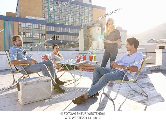 Friends having a rooftop party on a beautiful summer evening
