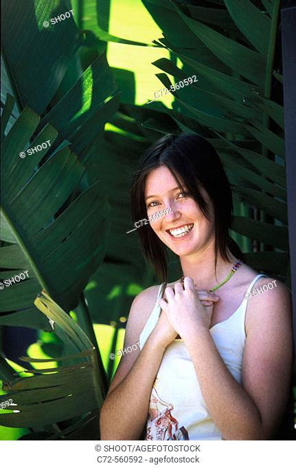 Young woman among tropical leaves