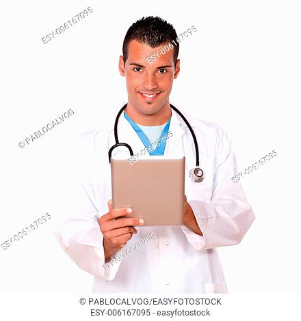 Portrait of charming male doctor working with his tablet pc while smiling at you and standing on isolated studio