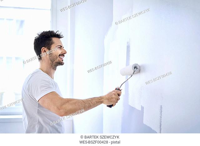 Smiling man painting wall in apartment