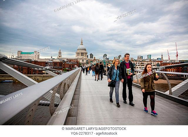 People walking across Millennium Bridge with St Paul's Cathedral in the background. London, United Kingdom, Great Britain