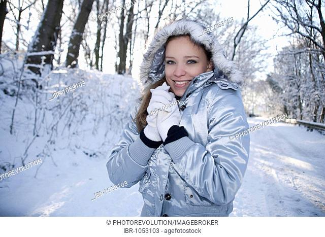 Portrait of a young woman wearing a hat and gloves in wintery landscape, freezing