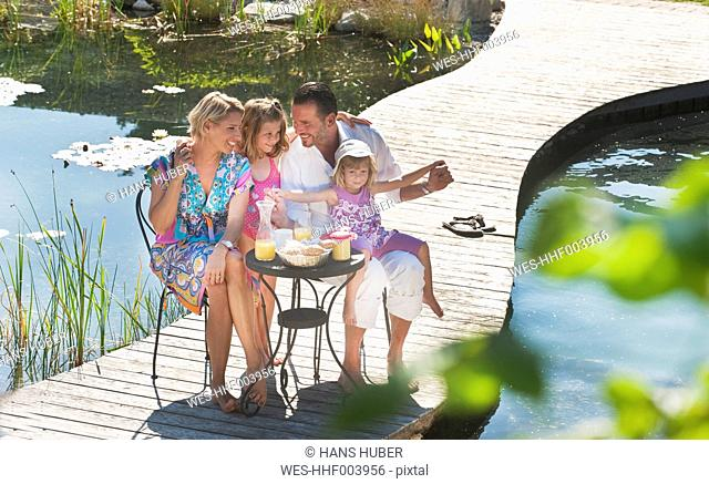 Austria, Salzburg County, Family having breakfast on bridge over pond