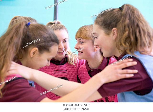 High school students talking in huddle before volleyball game