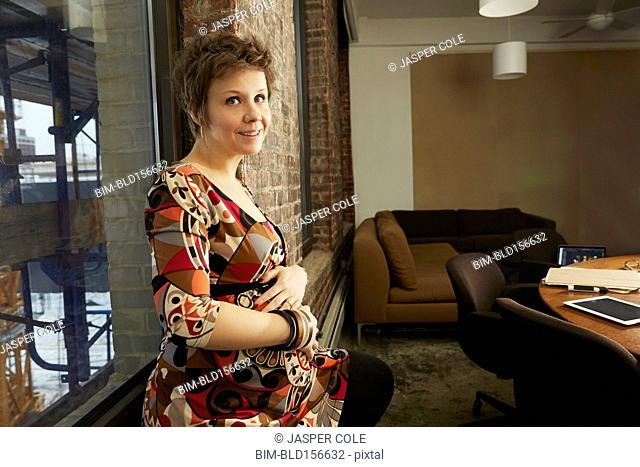 Pregnant businesswoman smiling in office