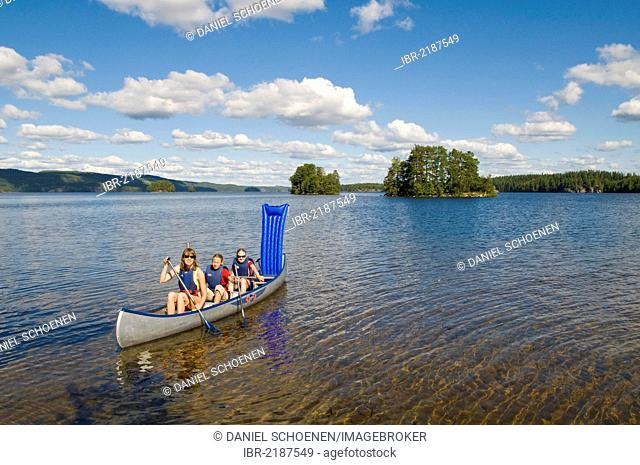 Family canoeing on a lake near Bengtsfors, Dalsland, Sweden, Europe