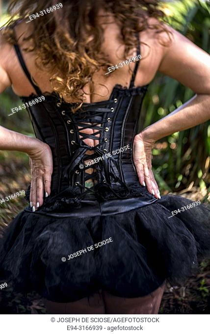 Back view of a woman wearing a black lace-up corset