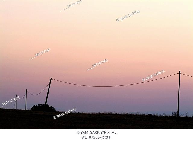 Three old electrical pylons at sunrise, Carcassonne, Alzonne, France