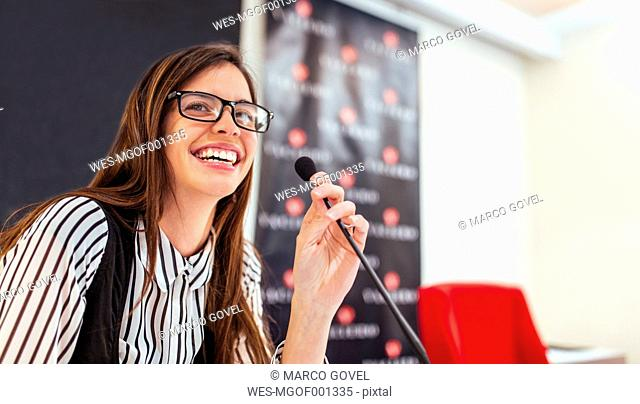 Portrait of laughing young businesswoman at microphone