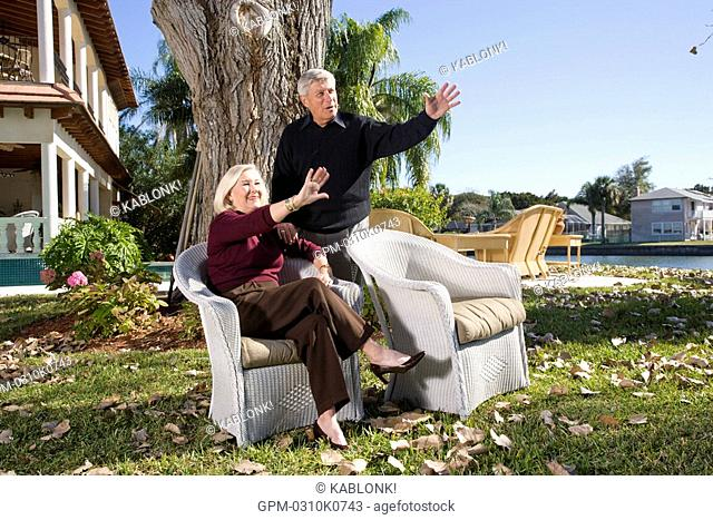 Portrait of senior couple waving in yard of luxurious home