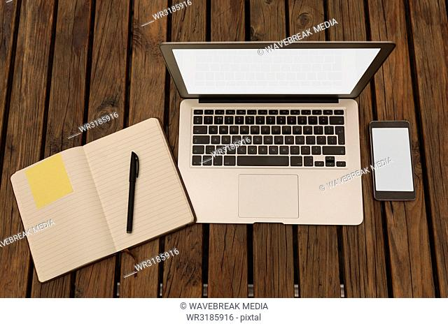 Laptop, diary, pen and mobile phone on table