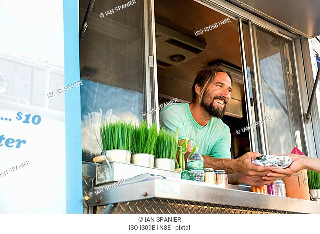 Man passing food out of hatch of fast food trailer