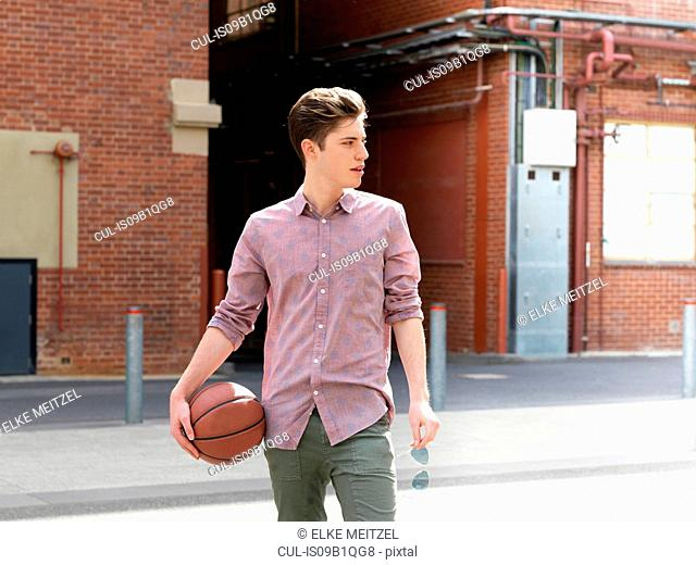 Young man outdoors, holding basketball and sunglasses, looking away