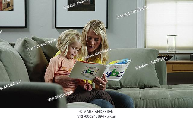 MS DS Mother reading to daughter (4-5) on sofa / Orem, Utah, USA