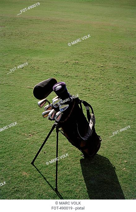 A golf bag and clubs on a golf course