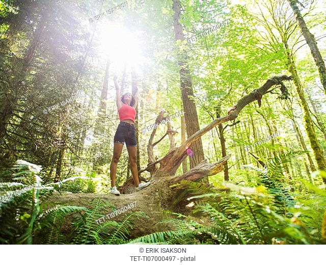 Young woman standing on log in forest