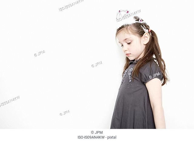Girl wearing tiara looking downcast