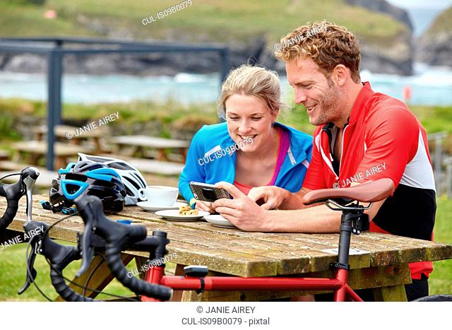 Cyclists using mobile phone at picnic table overlooking ocean
