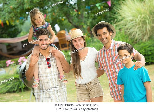 Happy family with barbecue in a garden, outdoors, France