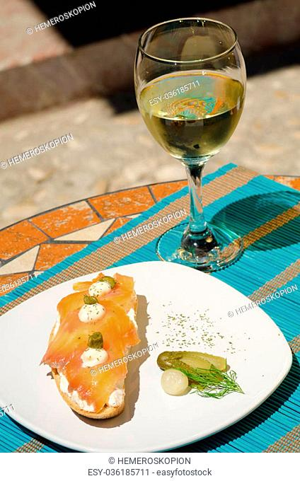 Tapa served with white wine on a sunny Andalusian terrace