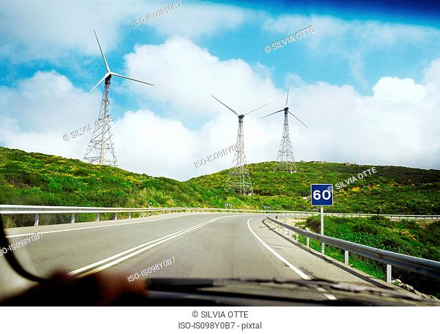 View of wind turbines and road through car windscreen
