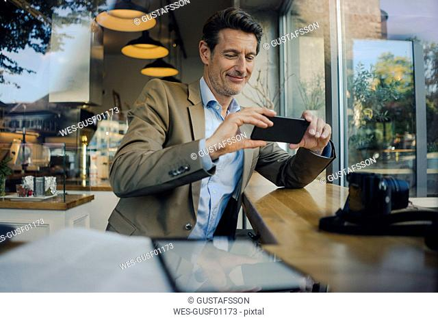 Mature businessman sitting in coffee shop, using smartphone