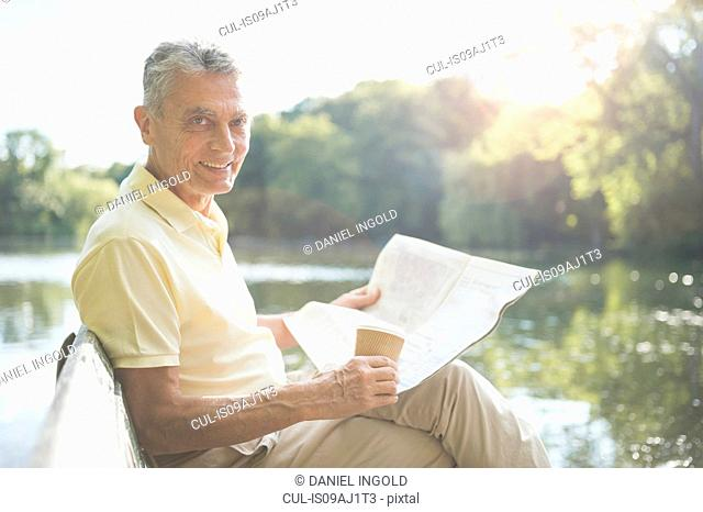 Senior adult man sitting by lake, holding coffee and newspaper
