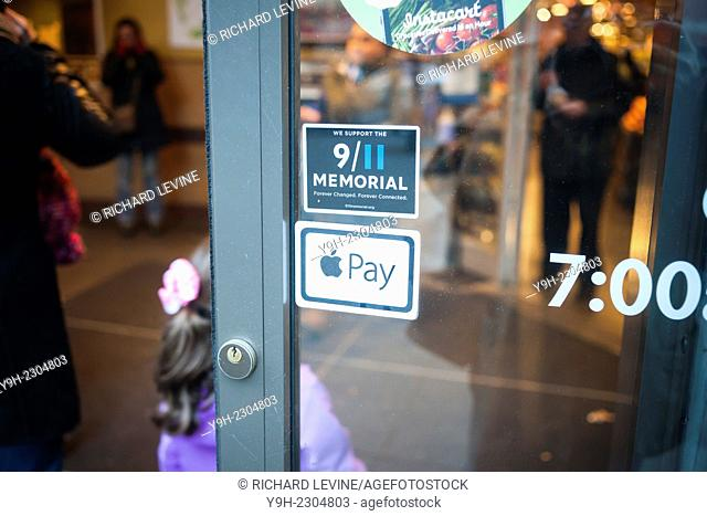 Signage in a Whole Foods Market in New York informs customers of their acceptance of the Apple Pay method of payment