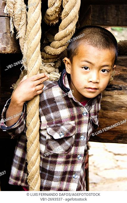 Portrait of Newar boy under the processional chariot of the Bisket Jatra New Year festival. Bhaktapur , Nepal