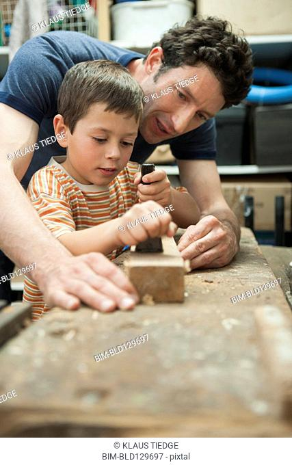 Caucasian father and son working in woodshop