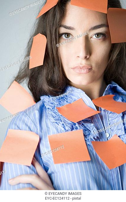 Portrait of a young woman covered with adhesive notes