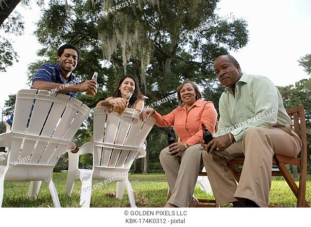 Mature couple having drinks with inter-racial couple while sitting on lawn chairs