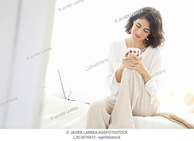 Woman sitting on bed with laptop computer and smiling