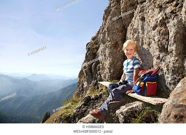 Germany, Bavaria, Boy 4-5 Years sitting on mountain summit, smiling, portrait