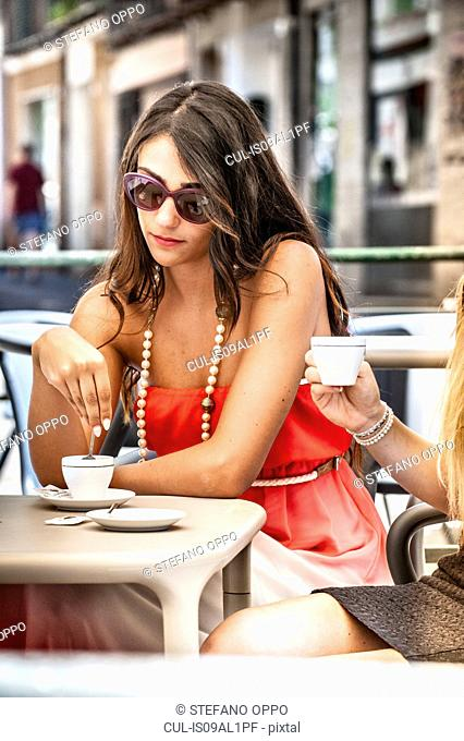 Two young female friends drinking espresso at sidewalk cafe, Cagliari, Sardinia, Italy