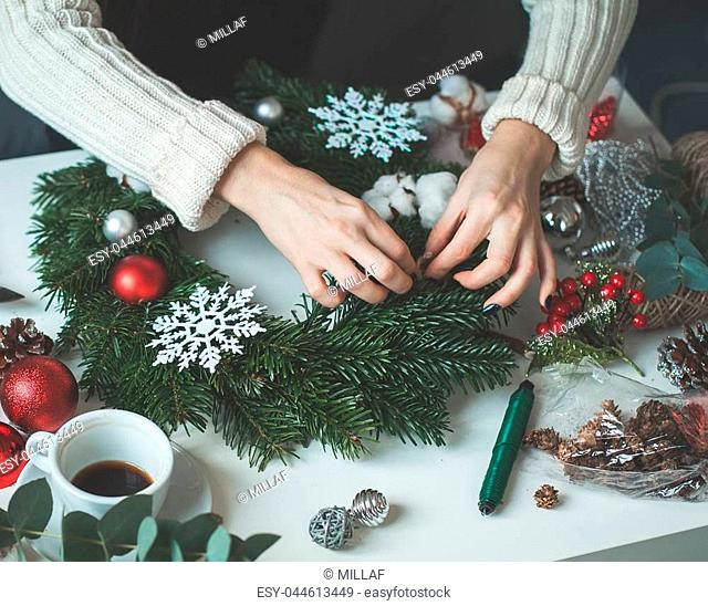 Christmas Concept with Evergreen Xmas Tree Twig, Red Glass Balls and Female Hands