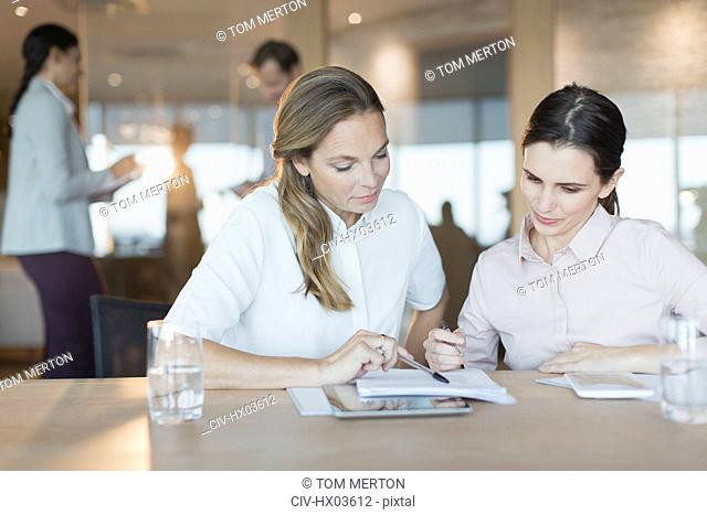 Businesswomen reviewing paperwork in conference room meeting