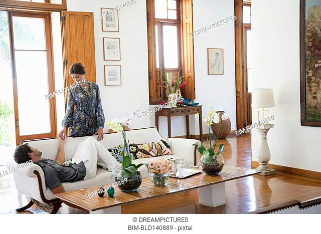 Hispanic couple relaxing in living room