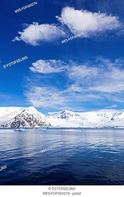 South Atlantic Ocean, Antarctica, Antarctic Peninsula, Gerlache Strait, View of iceberg with snow-covered mountain range