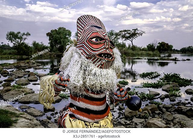 Man dressed as a Makishi posing to the camera by the Zambezi river bank. The Makishi is a character that for the northwestern peoples of Zambia living at the...
