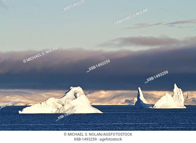 Early morning light catches icebergs in Neko Harbor on the western side of the Antarctic Peninsula during the summer months