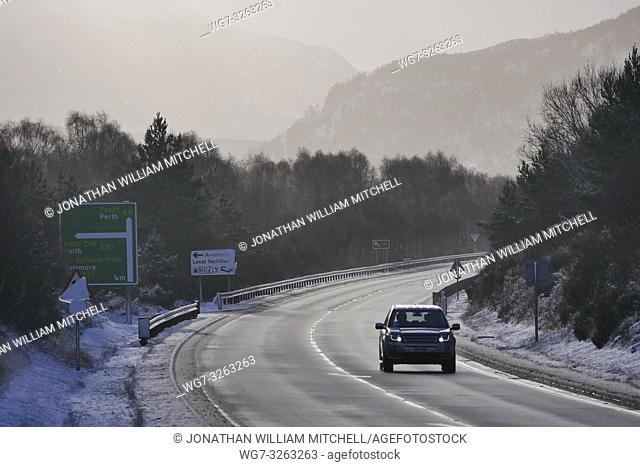 AVIEMORE, SCOTLAND, UK - 17 Jan 2019 - A driver braves the A9 amid a snowy landscape showing the snowy mountains of the Cairngorms near Aviemore Scotland UK...