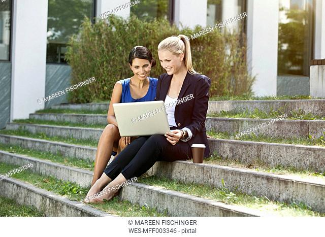 Two businesswomen sitting on stairs outside using a laptop