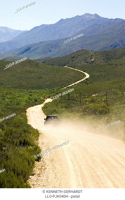 Car traveling along a dirt road with a cloud fo dust behind it. Swartberg Region, Calitzdorp, Western Cape Province, South Africa