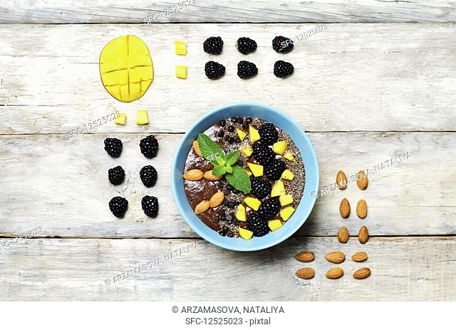 Chocolate smoothies breakfast bowl with chocolate chips, mango, blackberry, almond and Chia seeds