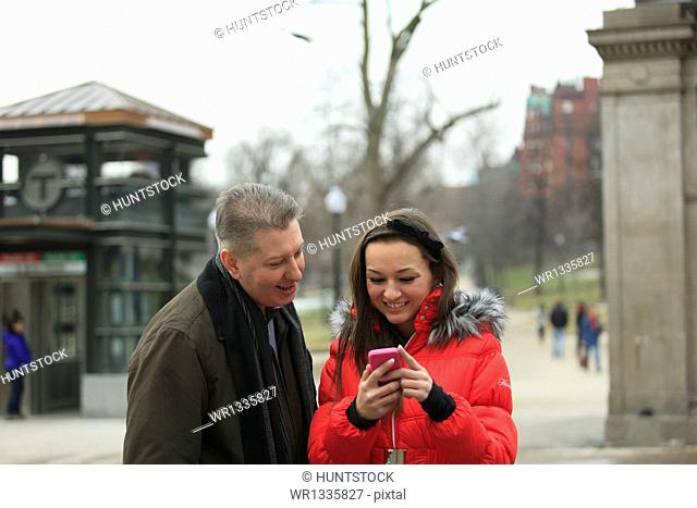 Couple looking at a cell phone on Tremont Street near subway station, Boston, Suffolk County, Massachusetts, USA