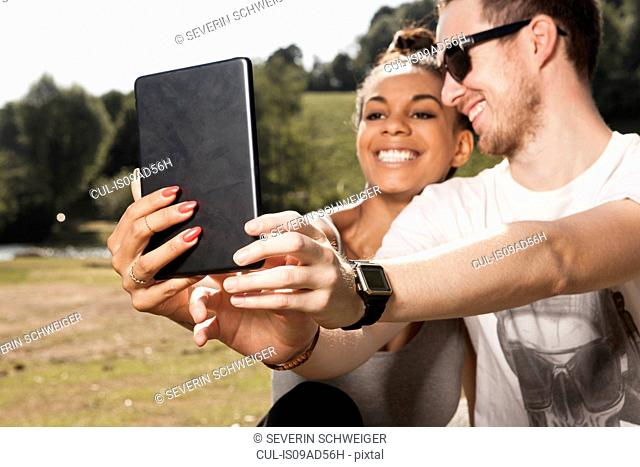 Young couple using digital tablet to photograph themselves