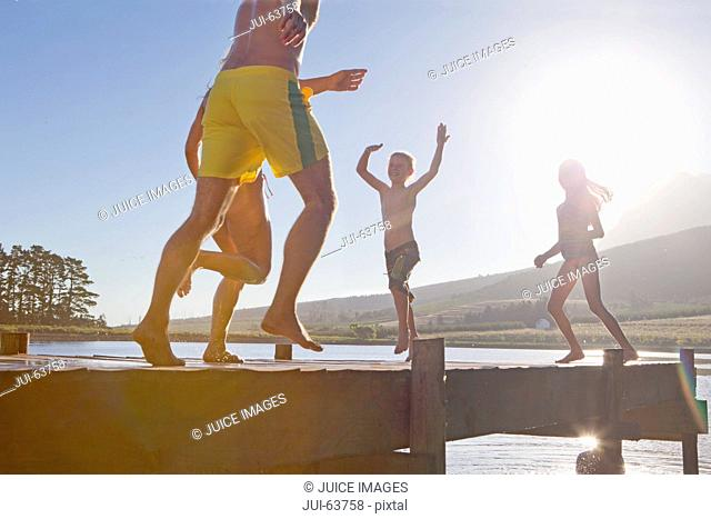 Happy family running and jumping on jetty