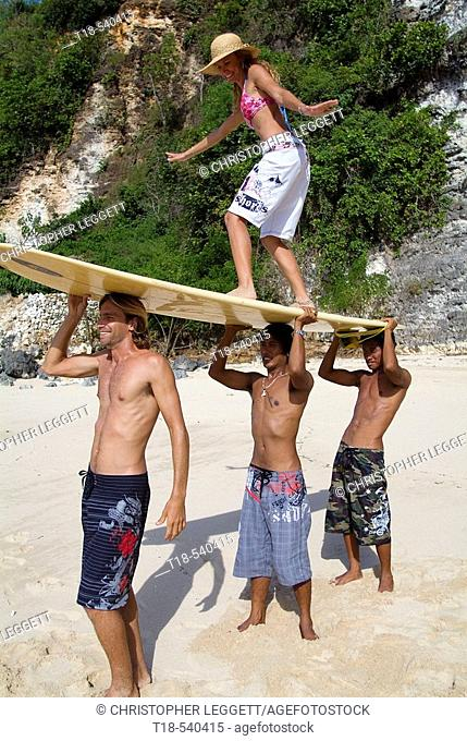 three young men lifting girl with surfboard