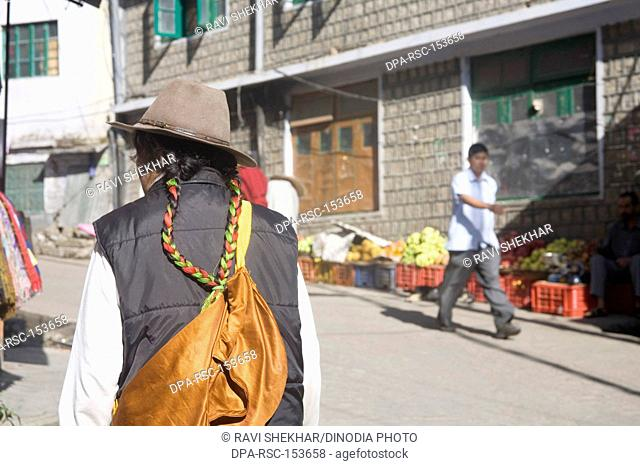 Tibetan woman in traditional dress walking on Jogibara road Mcleod Ganj ; Himachal Pradesh ; India